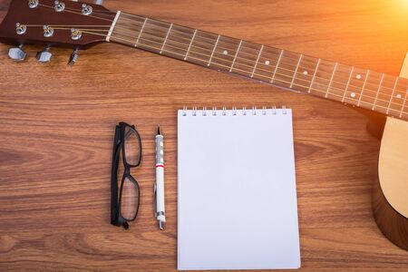 fingerboard: guitar notebook, pencil and eyeglasses on wooden background