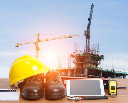 caja fuerte: Trabajando ingeniero mesa con tableta y las herramientas en la construcción de la grúa de construcción Foto de archivo