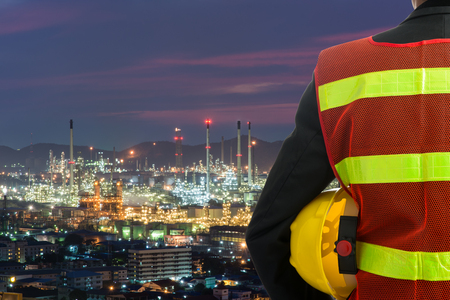 Hand or arm of engineer hold yellow plastic helmet in front of oil refinery industry Stock Photo