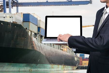 Engineering working hold conputer notebook in front of industrial harbor cargo Stock Photo