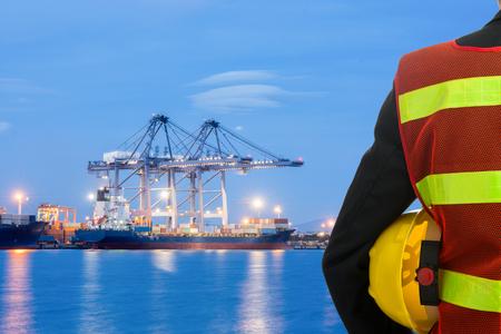 手やエンジニアの腕は貨物港の読み込みの前に黄色のプラスチック製ヘルメットを保持します。 写真素材