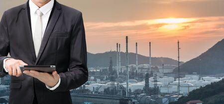 エンジニア リング作業油製油所発電所の前にタブレットを保持します。