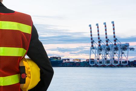 ingeniero: Mano o el brazo del ingeniero sostienen casco amarillo de plástico delante del puerto de carga de carga Foto de archivo