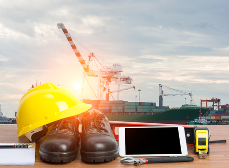 ingeniero: Trabajando ingeniero mesa con herramientas y la tableta en el puerto de carga con grúa Foto de archivo