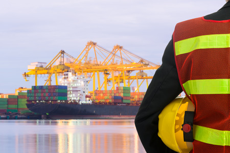 port: Hand or arm of engineer hold yellow plastic helmet in front of cargo port loading