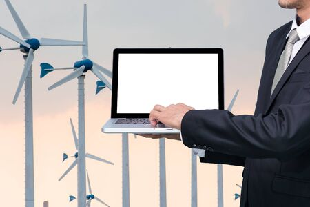conputer: Engineering working hold conputer notebook in front of Wind Turbine Power Generator Station