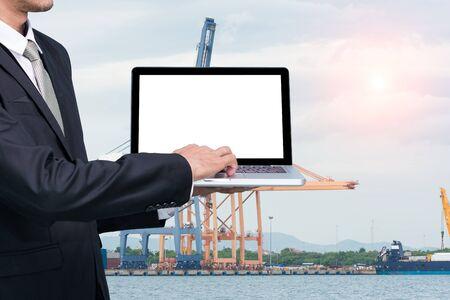 conputer: Engineering working hold conputer notebook in front of industrial harbor cargo Stock Photo