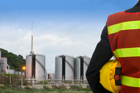 Hand or arm of engineer hold yellow plastic helmet in front of oil refinery industry Standard-Bild