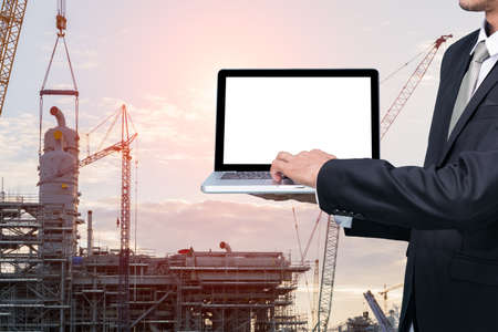 conputer: Engineering working hold conputer notebook in front of construction supervisor site Stock Photo