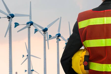 wind turbines: Hand or arm of engineer hold yellow plastic helmet in front of wind turbine Stock Photo