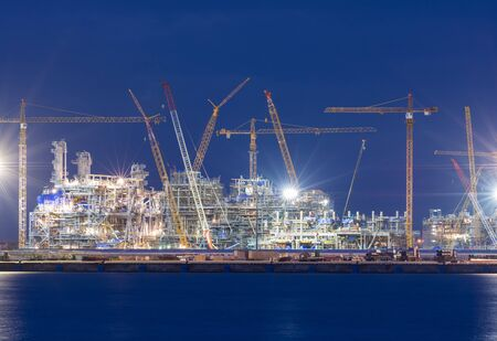 construction project: Industrial landscape with cranes on the sunset blue background