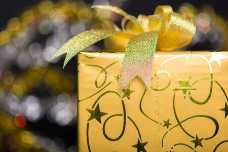 closed ribbon: golden gift box with bow, bokeh glittery black background