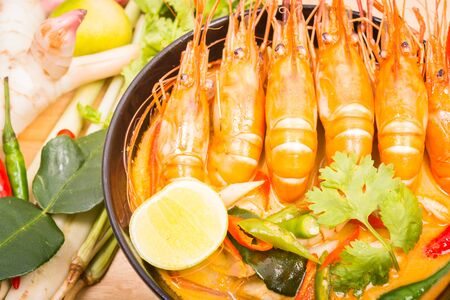 goong: Tom Yum Goong, Thai hot spicy soup shrimp on Black Cup with wooden table, Thailand Food