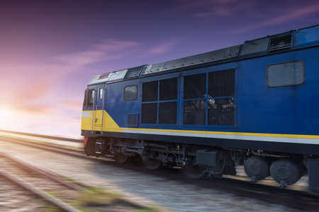 intermodal: Fast freight blue train at sunset with motion blur