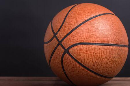 terrain de basket: Gros plan vieux de basket-ball basket-ball sur fond de bois et noir
