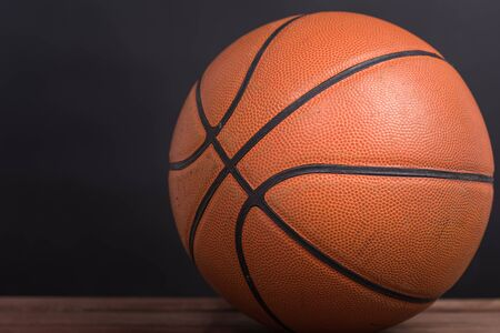 pista baloncesto: Primer vieja pelota de canasta de baloncesto en el fondo de madera y negro