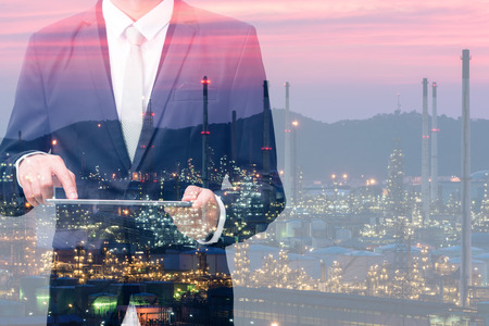 Double exposure with businessman touch on tablet and oil refinery industry plant, Petroleum