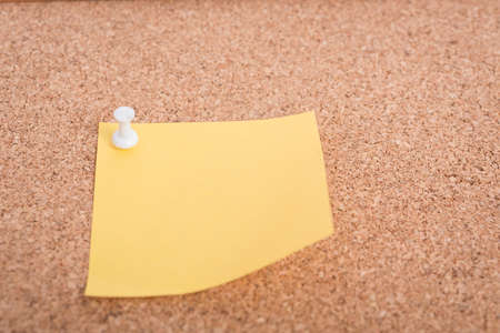 pin board: Yellow blank note papers with pin on wooden board background