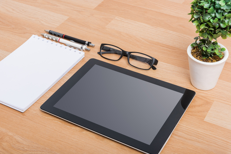 blank tablet: Top view Blank digital tablet with paper and pen on a wooden desk Stock Photo