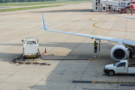 Airport man worker service refuelling the aircraft, runway