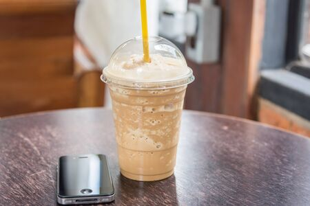coffee blender: coffee blender cappuccino and mobile phone on table in cafe shop Stock Photo