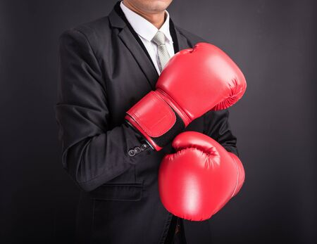 protective suit: Young businessman with boxing gloves isolated on black background