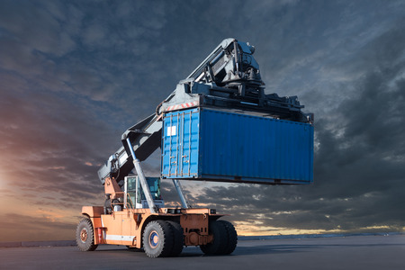 Carretilla elevadora que maneja la carga de la caja del envase en los muelles