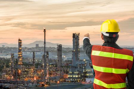 Ingeniería petroquímica hombre con casco de seguridad blanca de pie en la refinería de petróleo estructura del edificio industria petroquímica Foto de archivo - 84157323