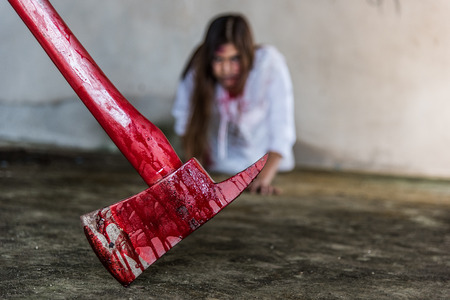 Zombie woman crawling on the floor and axe with bloody, halloween concept