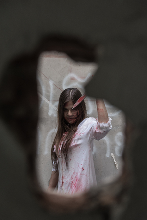 Zombie or Ghost woman with bloody in hole cement broken ,halloween concept Stock Photo