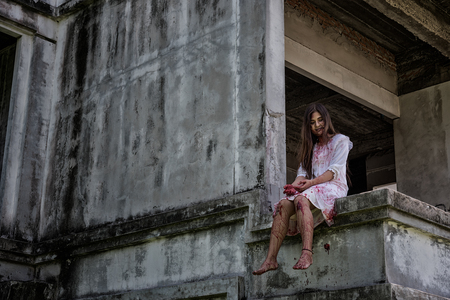 Zombie, Ghost, Woman murder with bloody sit wait for help on abandoned building ,halloween concept 版權商用圖片