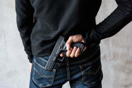 Back view man reaching hand gun attached, robbery, crime, kidnapping