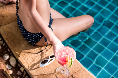 Beautiful Woman with cocktail glass near swimming pool blue water