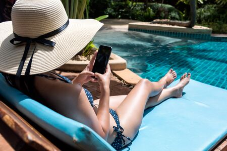 Young Beautiful lady wearing bikini using mobile phone sitting on chair in swimming pool blue water Stockfoto