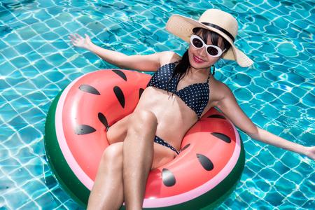 Beautiful girl Woman relaxing on watermelon lilo in pool, blue water