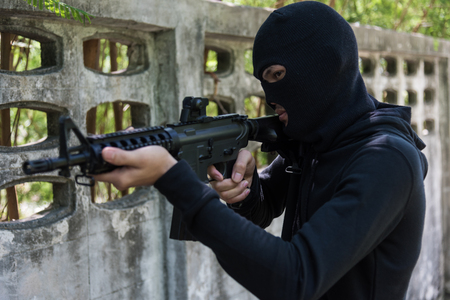 Robber assassin crime with hood holding M16 the gun points already shoot Stock Photo - 94703620