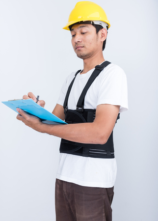 Worker Man stand write book note wearing back support belt body protect posture
