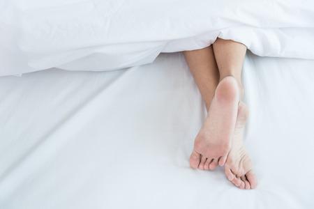 Woman Sleeping show feet on bed white blanket Foto de archivo