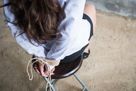 Detail young female hands tied wrist with rope sitting chair kidnapped concept