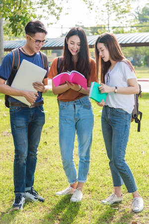 Happy group friends students standing in college reading school book together Standard-Bild