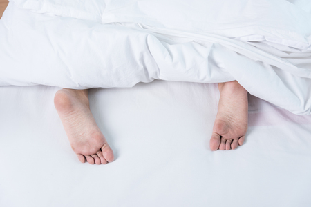 Woman Sleeping show feet on bed white blanket Banque d'images
