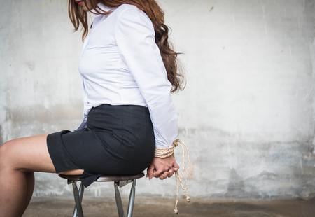 De handen van de vrouw met het concept van de de stoelontvoering van de kabelzitting worden gebonden die