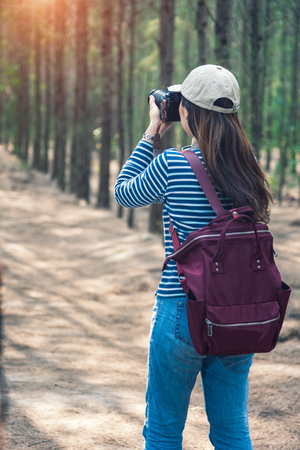 Young female woman lifestyle photographer travel taking photo in forest nature with backpack and copy space. Stock Photo