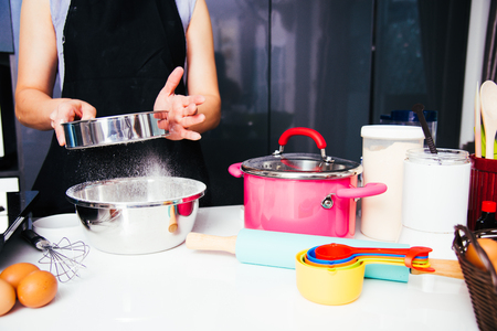 Woman girl in kitchen cooking baker bakery powder dough with baker sieve sifting Stockfoto