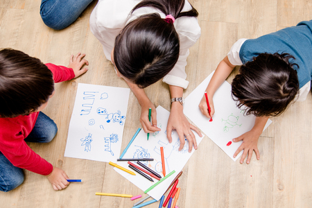 Top view Family happy children group kid boy and girl kindergarten paint drawing on peper teacher education at interior playroom Reklamní fotografie