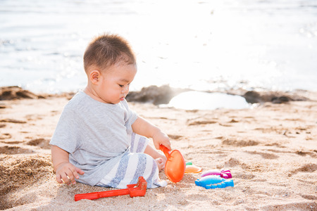 Baby boy playing sand on sea beach in vacation summer