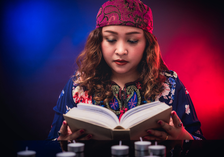 Female seer teller doing psychic reading book for predicting fate