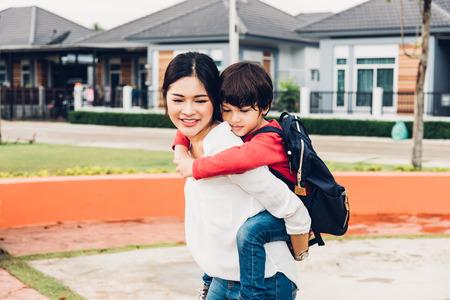 Family happy children kid son boy kindergarten ride back piggyback mother mom on park