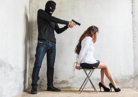 El ladrón ladrón apunta con la pistola a la cabeza está a punto de matar a la mujer rehén, crimen