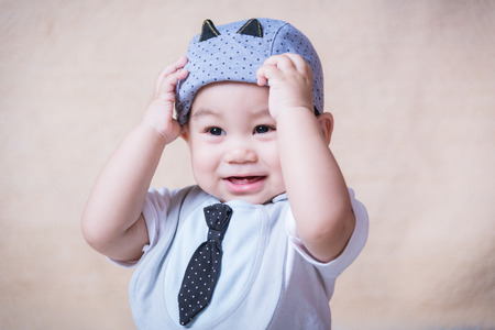 Asian baby boy holding a hat with necktie in studio
